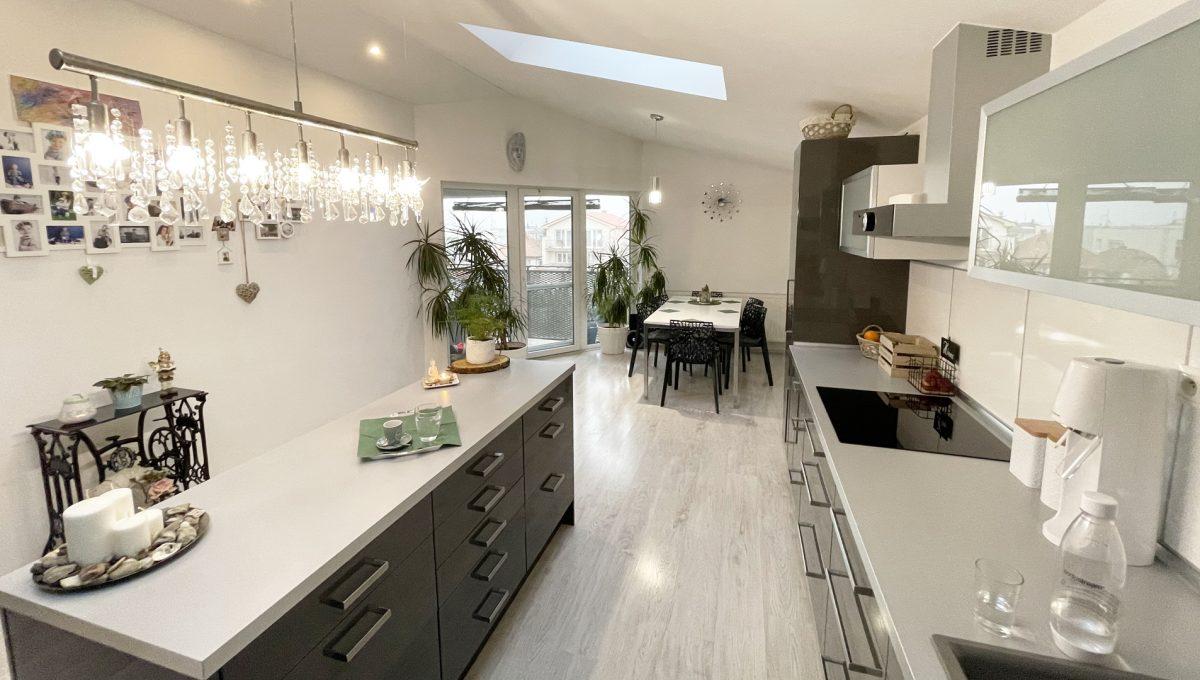 Konfido Nova Dedinka 7 izbovy rodinny dom dvojgeneracny sirsi pohlad na krasnu a priestrannu zariadenu kuchynu s jedalenskym kutom podkrovneho bytu