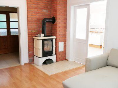 Miloslavov-01-3-izbovy-rodinny-dom-drevodom-obyvacia-izba-s-krbovou-pieckou-pohlad-smerom-na-vstup-do-chodby-a-vstup-do-kuchyne