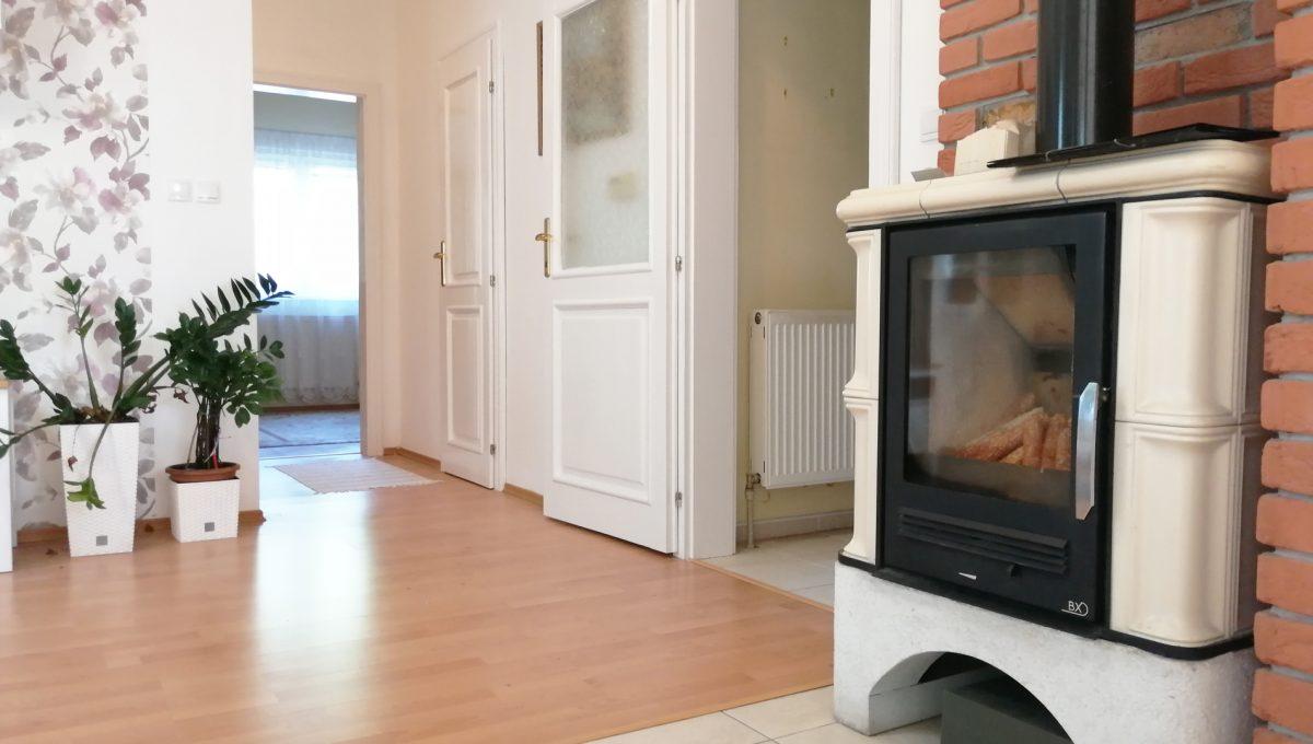 Miloslavov-04-3-izbovy-rodinny-dom-drevodom-pohlad-na-krbovu-piecku-v-obyvacej-izbe-so-vstupom-do-chodby-a-spalne