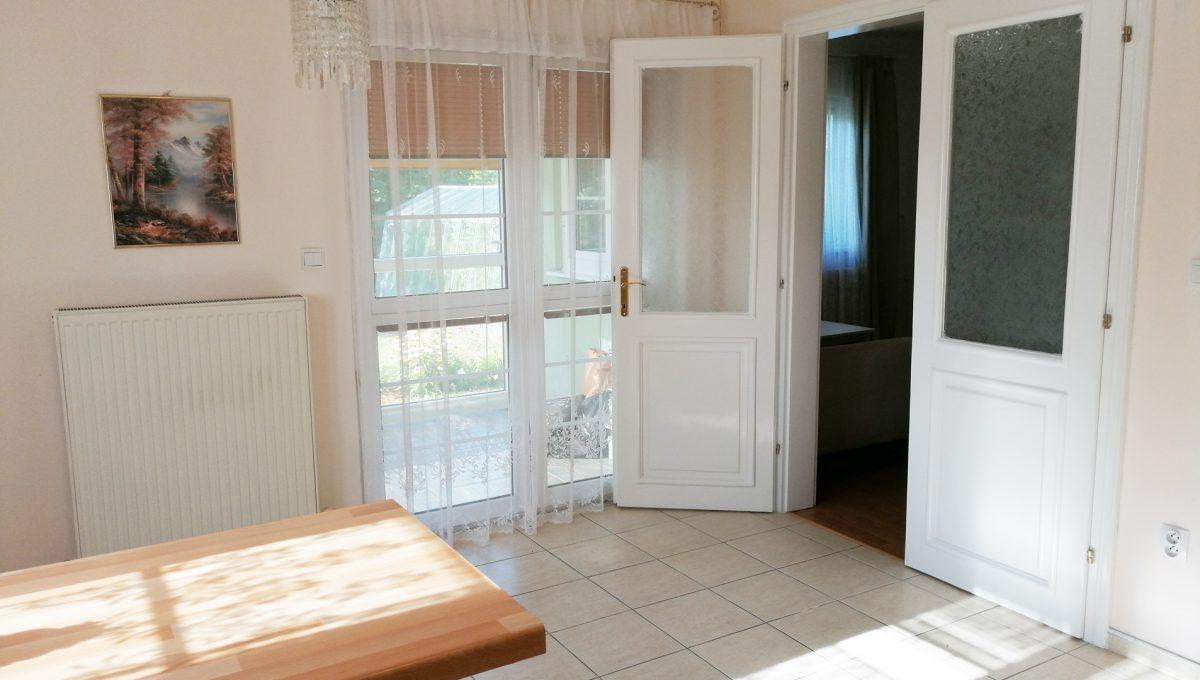 Miloslavov-07-3-izbovy-rodinny-dom-drevodom-pohlad-na-jedalensku-cast-zariadenej-kuchyne-s-vystupom-do-obyvacej-izby-a-na-zasklenu-terasu