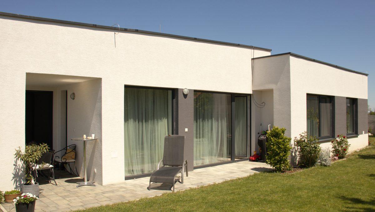 Miloslavov 22 rodinny dom 4 izbovy bungalov pohlad na cast domu s oknami do izieb a terasou so vstupom do obyvacej izby a kuchyne