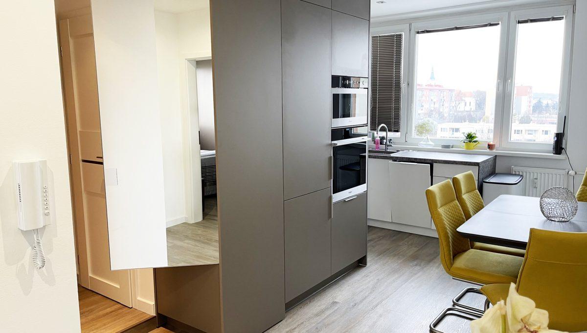 Senec 04 Sokolska ulica velmi pekny 3 izbovy byt na predaj pohlad na kuchynu s jedalenskym stolom a castou chodby s odkladacim priestorom so zrkadlom