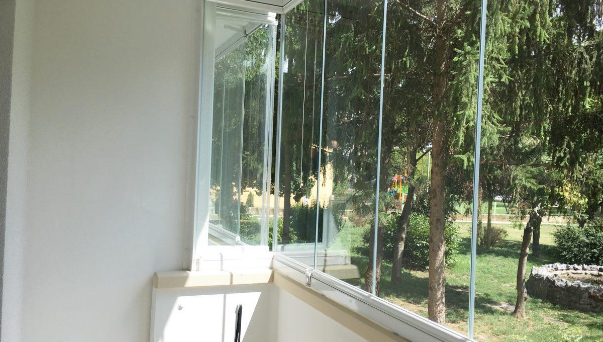 Senec 06 Kollarova 2 izbovy byt na prenajom pohlad na presklenu lodziu s vyhladom na stromy a ihrisko za bytovym domom