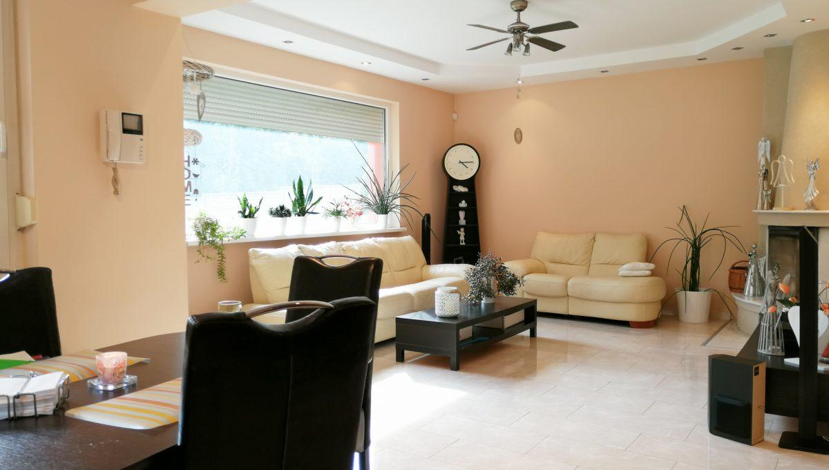 Turen 02 na predaj 6 izbovy rodinny dom pohlad z kuchyne na jedalensku cast obyvaciu izbu s krbom so sedacou supravou s velkym oknom s vyhladom na zahradu